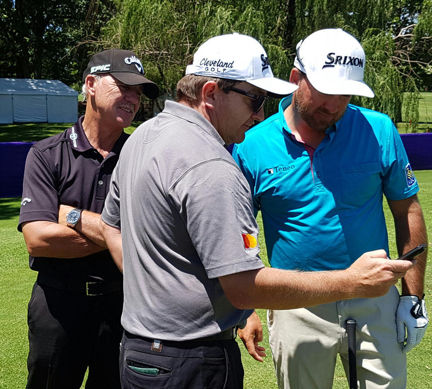 Caddy Ken Comboy shows McDowell and coach, Pete Cowen the video he took of Cowen in the rough at Erin Hills